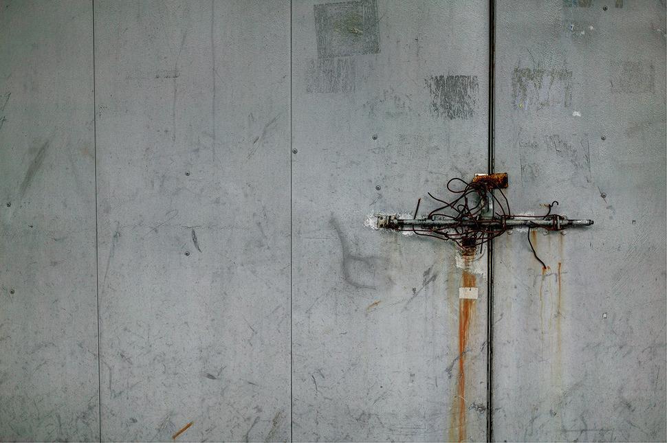 굳게잠긴 철문에 철사로 여러번 덧 감아놓은 자물쇠