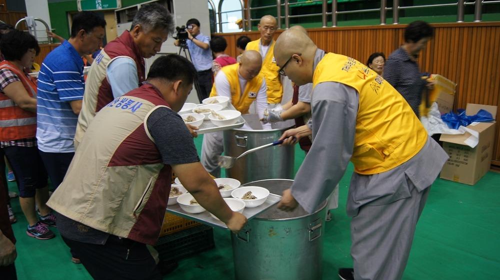 마이산 탑사와 쌍봉사가 주최한 문화 및 전문 봉사활동 행사에서 스님과 자원봉사자들이 어르신들에게 대접할 공양을 배식하고 있다
