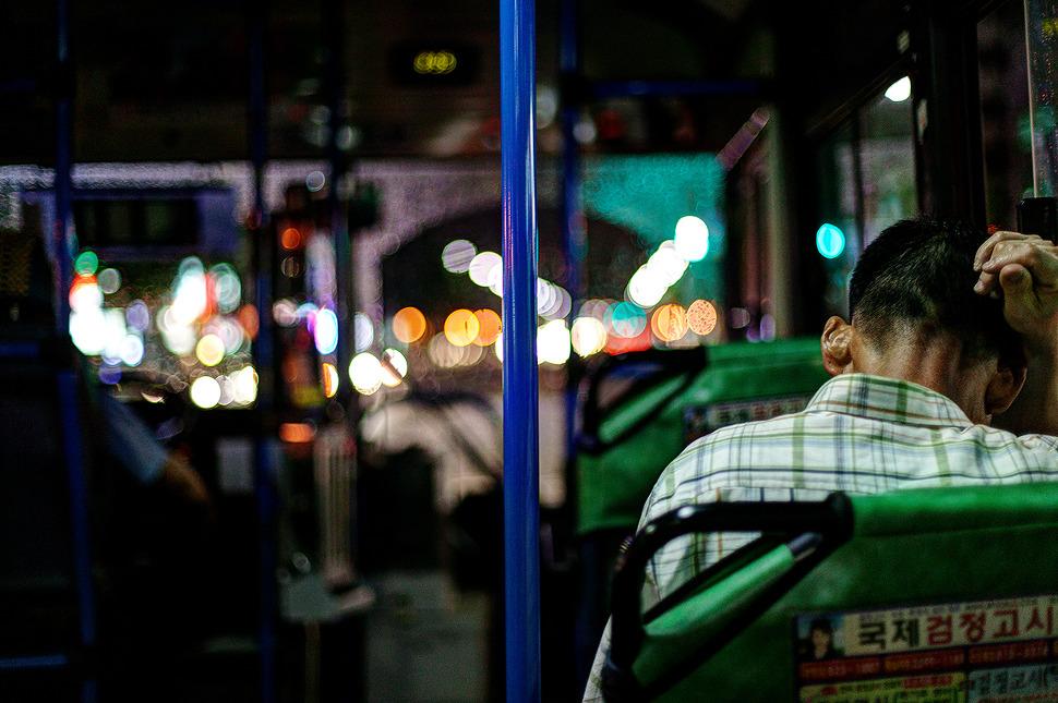 이른저녁에 고단하셨는지 버스좌석에서 한쪽팔을 괴고 잠을 청하는 아저씨 사진.