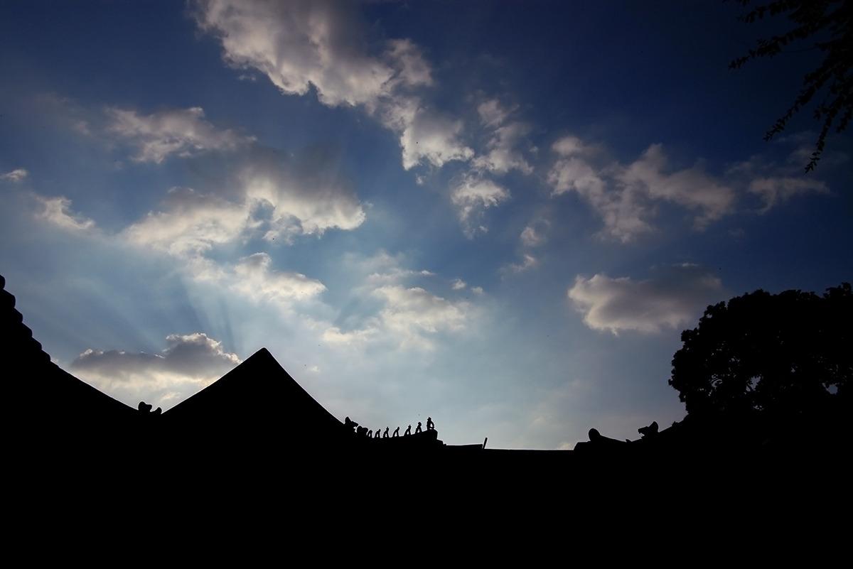 (경복궁사진) 역광으로 촬영되어 여러채의 건물실루엣이 하나처럼 보이고 그 뒤로 파란 하늘과 구름이 보인다. 삼장법사와 졸개를 뜻하는 어처구니구(잡상)이 도드라지게 표현되어있다.