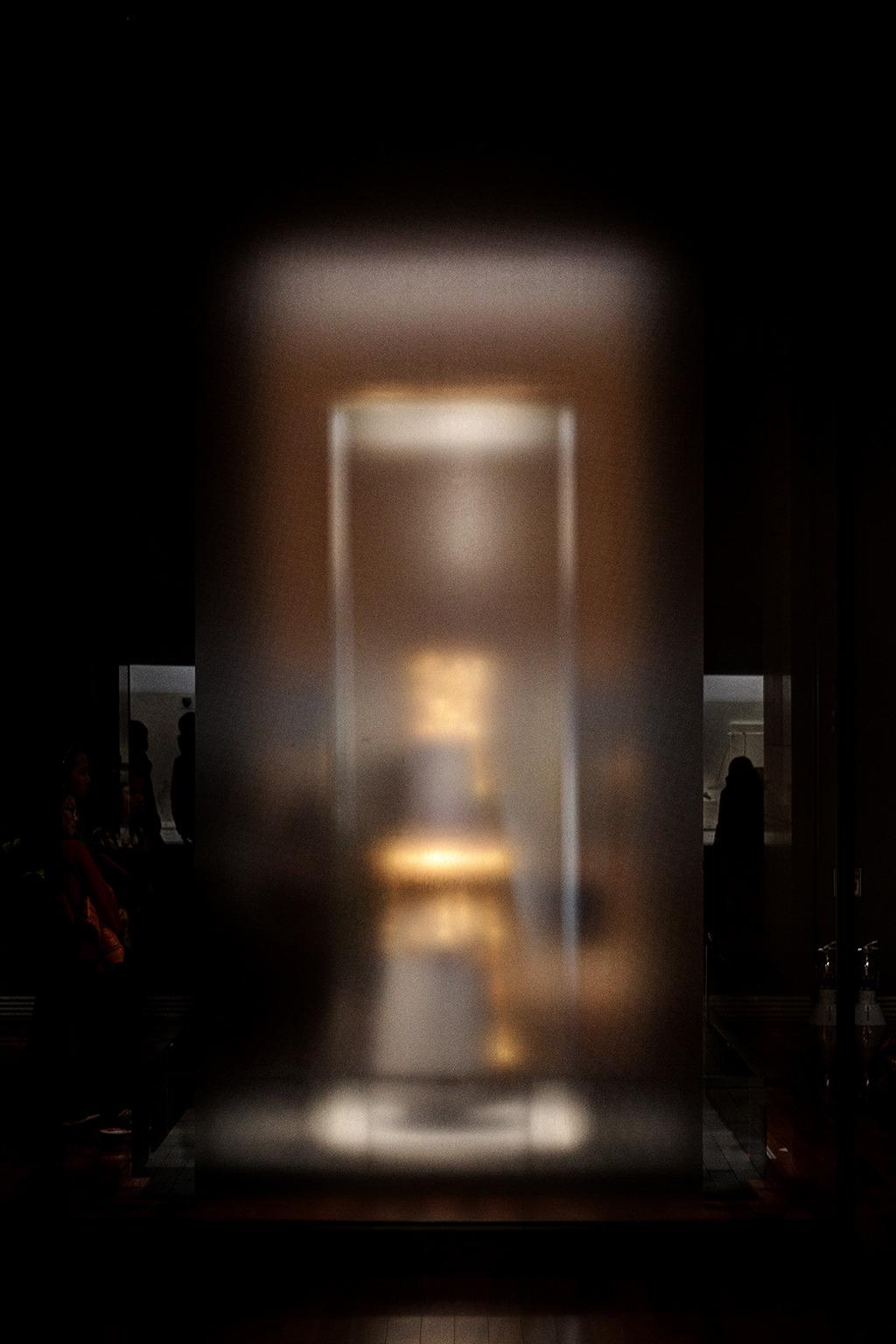 불투명유리 안쪽에 흐릿하게 금빛모양만 남아있는 무엇이 있고 주변에는 그것을 구경하는 사람들이 보인다.