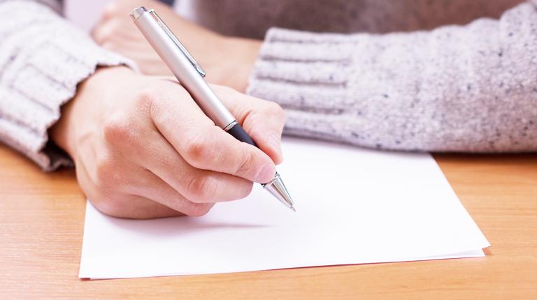 손으로 편지를 쓰는 모습
